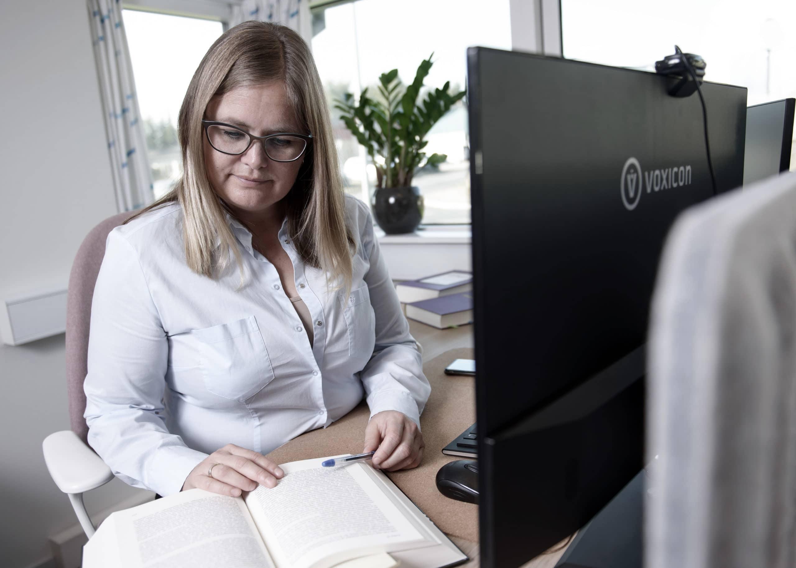 kvinde ved skrive bord læser i bog